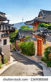 View of cozy old narrow street and traditional Korean houses of Bukchon Hanok Village in Seoul, South Korea. Seoul Tower on Namsan Mountain is visible on blue sky background. Scenic cityscape.