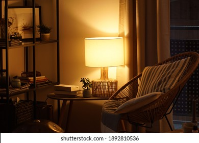 View of a cozy reader's corner with a table lamp spending warm light