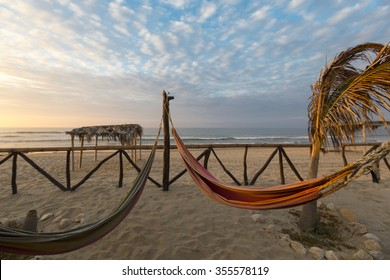 View of cozy straw hammocks on a tropical white beach with sunset light, Punta Sal near Mancora in Peru.