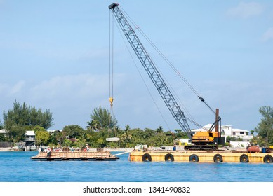 The view of a crane on a platform lifting the block in Nassau Harbour with Paradise Island in a background (Bahamas).