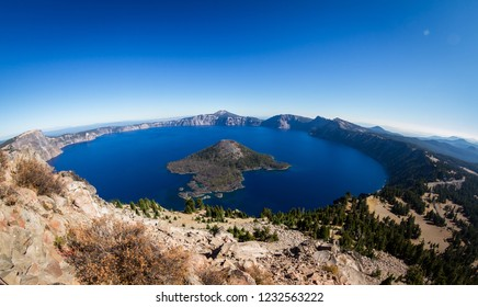 View of Crater Lake and Wizard Island from the Watchman tower lookout on a sunny cloudless autumn day with only a faint hint of smoke in the horizon from seasonal forest fires.