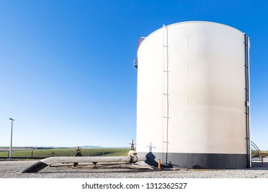 View of the crude oil storage tank and pipeline. Storage tanks are often cylindrical in shape, perpendicular to the ground with flat bottoms, and a fixed flangible or floating roof.