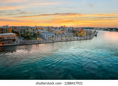 View from a cruise ship as the Piazza Vittorio Emanuele II fills with tourists enjoying a late summer evening sunset at the port city of Brindisi Italy on the Adriatic Coast in the Puglia region.