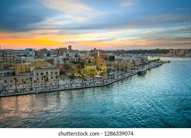 View from a cruise ship as the waterfront promenade fills with tourists enjoying a late summer evening sunset at the port city of Brindisi Italy on the Adriatic Coast in the Puglia region.