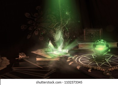 View of crystal ball and tarot card with smoke on the table. Dark tone. Under candlelight.