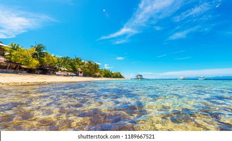 View of crystal clean water with a boat over coral reef in Moalboal, Cebu, Philippines. Copy space for text