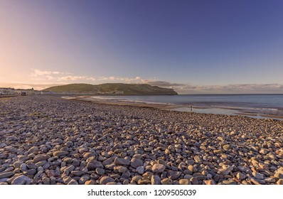 A view of Llandudno's curving shoreline lined by white fronted hotels at dusk.  The Great Orme headland is in the distance and a fading blue sky is above.