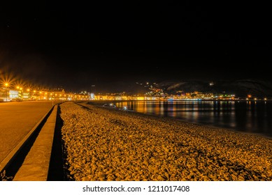 A view of Llandudno's curving shoreline lined by white fronted hotels at night.  The Great Orme headland is just visible in the distance and a night sky is above.