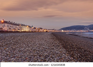 A view of Llandudno's curving shoreline lined by white fronted hotels at sunrise.  The Great Orme headland is in the distance and a dawn sky is above