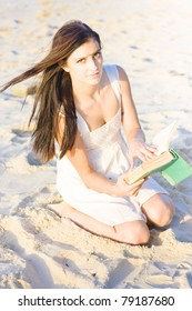 View Of A Cute Woman Reading A Book In The Sand At A Tropical Island Beach Resort