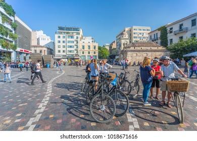 View of cyclists and shoppers and Greek Orthodox Church in Monastiraki Square, Monastiraki District, Athens, Greece, Europe 12 October 2017