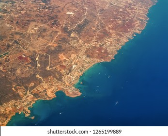View of Cyprus from airplane's porthole. Airplane view over Cyprus, relief of the island and beautiful turquoise Mediterranean with boats and ships in the waters. Airplane wings in the early morning
