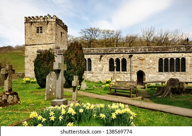 View of daffodils in the grounds of the historic church of St Michael and All Angels in Hubberholme, Upper Wharfdale, Yorkshire .