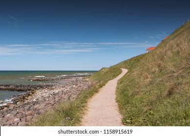 View of the danish beach coastline with green grass dunes during bright daytime and blue sky perfect for summer. Danish Beach, Lokken, Lønstrup in North Jutland in Denmark, Skagerrak, North Sea