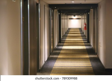 View of a dark corridor with leading lines. The space is empty and nobody can be seen. Form as a tunnel with rectangles in perspective. Convergence of lines in the direction of a light at the end.