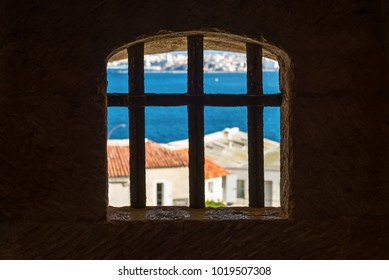 View from the dark prison cell. Detail of a window with wrought iron grating (Castle grill) and view to blue sea of an ancient castle.