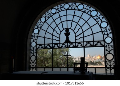 View from the dark room of the monastery of the Virgin through a metal grid with a cross to the Golden Dome of the Rock, Jerusalem, Israel.