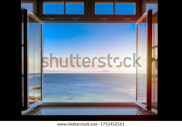 view from a dark room at sea during sunset through an open window