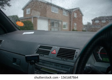 view from dashboard with rain on windscreen