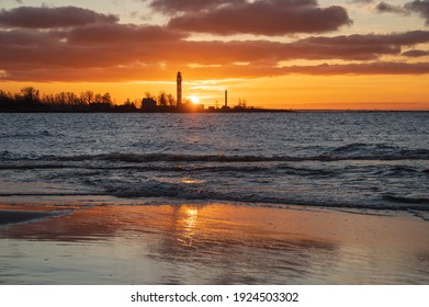 View to the Daugavgriva lighthouse from Mangalsala pier against colorful sunset sky
