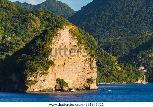 The view from the deck of a cruise ship ae steep rocky peaks of the Pitons in St. Lucia island at sunset.