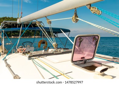 View from the deck of luxury white sailing yacht to the beach on a tropical island. Blue calm southern sea from charter bareboat yacht. Rigging, mast and open hatches on a sunny day. Phuket, Thailand