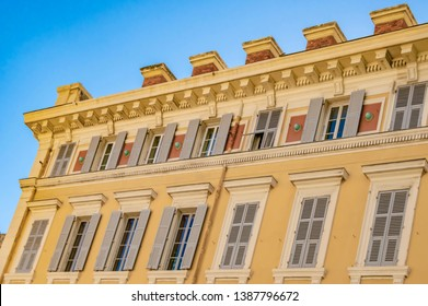 View to the decorated facade of a historic house in Nice, France. You can see the typical windows and shutters of a Mediterranean cityscape.