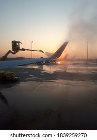 View of the deflation process of an aircraft wing through the aircraft window at sunrise in winter