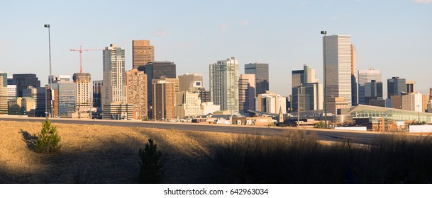A view of Denver behind a highway on ramp at sunset