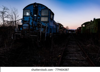 A view of derelict Conrail locomotives at sunset at an abandoned train railroad yard in Ohio.