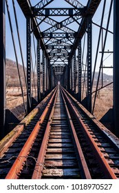 A view of derelict, unused tracks on the Scioto River bridge along the Norfolk Western Railway Portsmouth Subdivision in the Appalachian Mountains near Portsmouth, Ohio.