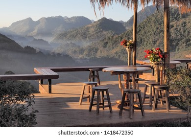 view of desks and chair on terrace in tea shop with green mountain background, Rai Cha 2000 Tea farm Plantation, popular attraction in Doi Ang Khang, Chiang Mai, northern of Thailand.