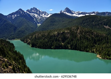 View of Diablo Lake with Kayakers and Mountains in the North Cascades National Park, Washington State in Bright Color