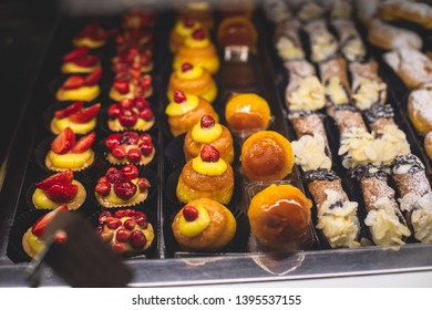 View of different traditional italian pastry candy desserts assorment, with cannoli, panna cotta, tartufo, amaretti, panettone, zeppole bomboloni, semifreddo, cartocci and others in Rome, Italy