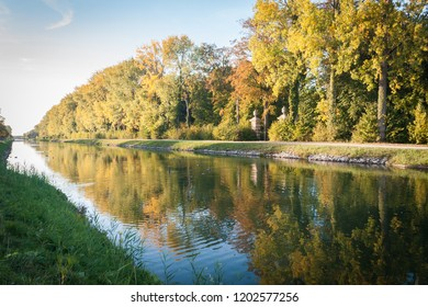 A view of the Dijle River Bike Path between Leuven and Mechelen, Belgium, on a sunny day in autumn with colorful foliage and reflections.
