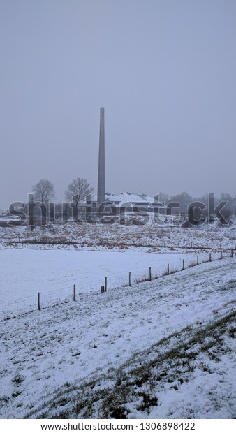 view from a dike at a brickworks with tall chimney in the frozen floodplains of the river Rhine - vertical shot. The Netherlands, winter 2019. fluvial landscape