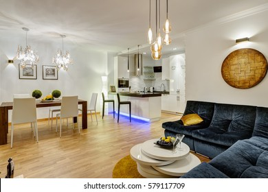 View of dinning room in green white and dark blue colors with creative things. Flowers and fruits on table and  big cozy sofa in corner of room. Two crystal chandelier of ceiling.