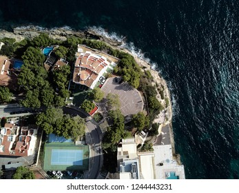 View directly from above coast and Mediterranean Sea. Summer luxury villas with swimming pools parking area sport tennis field. Mallorca or Majorca, Balearic Islands Spain