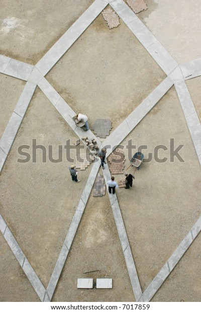 view from directly above of construction workers standing making decision which brick material to use