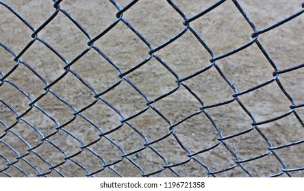 View of dirt infield of baseball field through chain link fence
