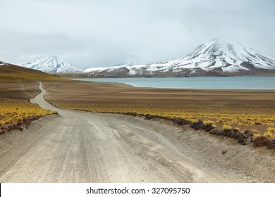 View of dirt road and Miscanti lagoon in Sico Pass, Chile