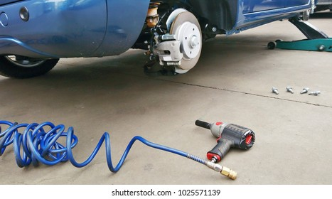View of a disc brake during tyre replacement and pneumatic air screwdriver on the ground. Car maintenance.
