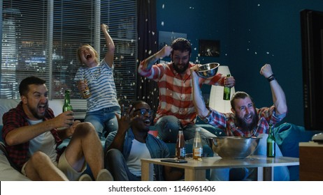View of diverse men and woman with beer and popcorn spilled cheering for winner team while watching sport game