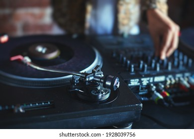 View of Dj mixer and vinyl plate with headphones on a table with DJ playing and mixes the track in the background, during night techno party in nightclub
