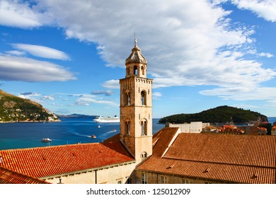 View of Dominican Monastery in Dubrovnik with classic red tiled rooftops, and Adriatic sea with passenger ship and boats near Croatian islands.