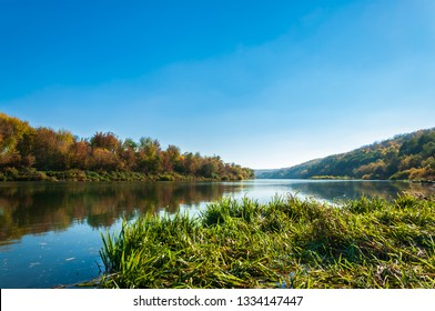 View of the Don River with hilly banks overgrown with reeds, covered with colorful autumn forest and lit by the evening sun on the cloudless blue sky background