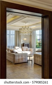 View from door of modern interior of empty living room in brown, white,beige colors. Three sofas with pillows, crystal chandelier in the center of ceiling. Beautiful view fro window in garden.