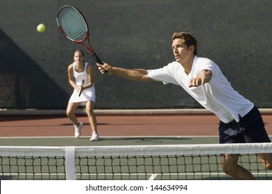 View of doubles player hitting tennis ball with forehand near net on court