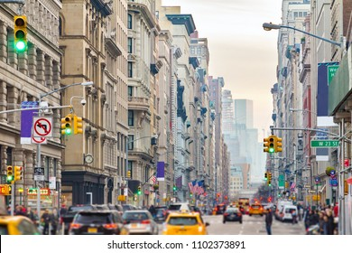 View down Broadway in New York City with people and cars lining the street through Midtown Manhattan