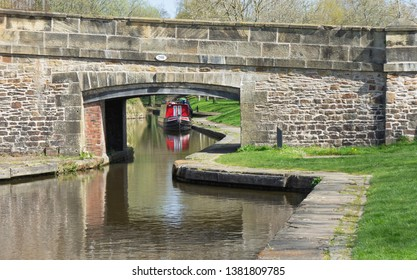 A view down a canal and under an old stone bridge at Llangollen Wharf, Wales, with a red narrowboat moored up on the other side complete with reflection